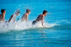 Boys surfers surfing running jumping on surfboards Royalty Free Stock Photography