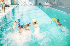 Boys swimming with plank in a pool race. Children in water with plank are doing swim exercise. Healthy sport activity in pool. Sportive kids activity in modern Stock Image