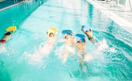 Boys swimming with plank in a pool race. Children in water with plank are doing swim exercise. Healthy sport activity in pool. Sportive kids activity in modern Stock Photo