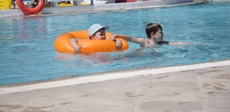 Boys in swimming pool. Two boys in swimming pool with ring buoy Royalty Free Stock Photography