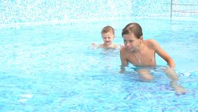 Boys swimming in the pool at the resort. 1 stock video