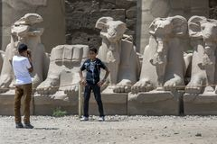 Boys take photographs in front of stone carved ram statues at the Temple of Karnak in Luxor in Egypt. Stock Photography