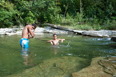 Boys taking a bath in the river. Boys playing with the river current stock image