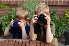 Boys taking photos. Brothers taking photos outside in the garden Royalty Free Stock Photo