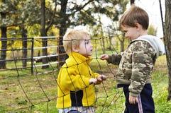 Boys talk through a fence. Two boys talk to each other through a fence on a farm royalty free stock image