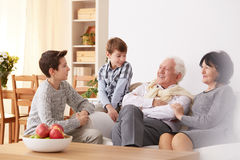 Boys talking with grandparents. Smiling boys talking with their grandparents in a living room royalty free stock photo
