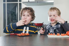 Boys tasting tomato Stock Photo