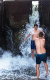 Boys, teenagers are playing under the waterfall, in the river. Wet and happy. On a warm summer day Royalty Free Stock Image