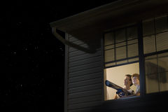 Boys With Telescope Looking At Night Sky. Young boys with telescope at open window looking at night sky Stock Photo