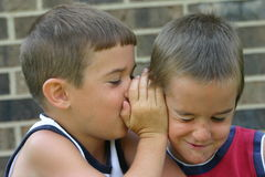 Boys Telling Secrets. Boy whispering in another boys ear and him making a funny face Royalty Free Stock Images