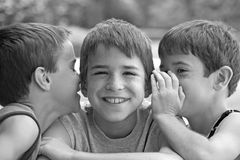 Boys Telling Secrets. In Black and White Royalty Free Stock Image