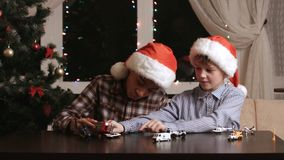 Boys with toys on Christmas. Two kids playing at night. Small-scale traffic accident. Driver's problems in miniature stock video