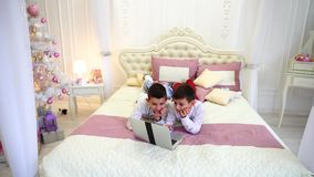 Boys twins posing and playing on laptop, lying on bed in bright room with Christmas tree in daytime. stock video