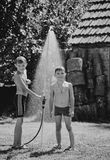 Boys under a shower Stock Photos