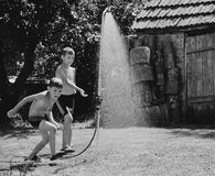 Boys under a shower in the garden Royalty Free Stock Photography