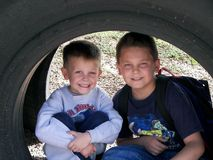 Boys under tire. Two boys posing under a tire at a school playground Stock Photos