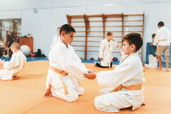 Boys in uniform practice martial art. Little boys in uniform practice kid judo. Young fighters on training in gym, martial art for defense royalty free stock images