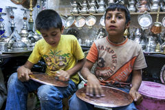 Boys in Urfa Bazaar in Turkey. Boys polishing copper ornaments in the Urfa (Sanliurfa) bazaar in the south east of Turkey Royalty Free Stock Photography
