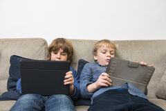 Boys Using Digital Tablets On Sofa. Boys playing online games on digital tablets while relaxing on sofa at home Royalty Free Stock Image