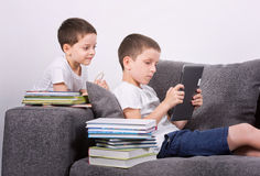 Boys using a tablet PC on the sofa. Stock Images