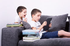 Boys using a tablet PC on the sofa. stock photos