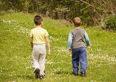 Boys walking. Boys are walking through a grassy field Stock Photos