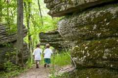 Boys walking in the forest. Two boys walking on a trail in the woods between large boulders Royalty Free Stock Photo