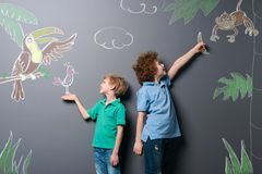 Boys walking through tropic forest. Two brothers feeding beautiful exotic birds and monkey drawn with chalk on a gray wall stock photo