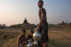 Boys was waiting to carry water pot back home with temple as background royalty free stock photo