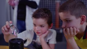 Boys watches for lightning inside electric lamp holding it over Tesla coil. Children makes physical experiment with Tesla coil in scinetific museum. Boys stock footage