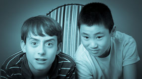 Boys watching an intense movie. Two teen friends watching an exciting movie Stock Images