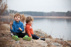 Boys watching lake with rocks Stock Images