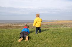 Boys watching sailing ships. Two brothers on a dike watching the sailing ships in the distance Stock Images