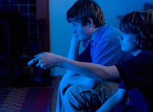 Boys watching TV. Boys (brothers) watching television, looking bored and changing channels Stock Photography