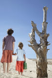Boys With Watering Can Standing By Dead Tree Royalty Free Stock Images