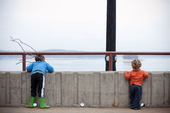 Boys wating the lake with sticks Royalty Free Stock Image