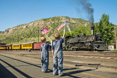 Boys waving American flags train departure Stock Images