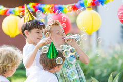 Boys wearing birthday hats. Playing outdoors, letting soap bubbles Royalty Free Stock Image