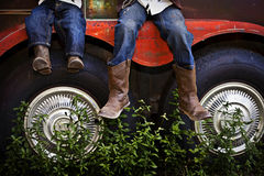 Boys wearing Cowboy Boots. Little boys wearing cowboy boots and jeans hanging off of the edge of horse trailer. Childhood Stock Photos