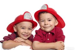 Boys Wearing Firefighter Hats. Two brothers aged 4 and 5 years old wearing firefighter helmets, isolated on white background royalty free stock photography