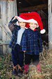 Boys wear cowboy boots and Christmas hat. Two young children wear a giant Santa hat with an old barn background stock photo