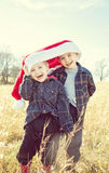 Boys wearing a giant Christmas Santa hat Royalty Free Stock Image
