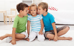 Boys whispering to a girl. Childish secrets - indoors scene Royalty Free Stock Images