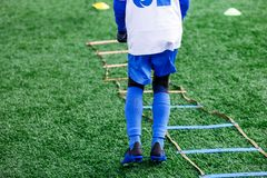 Boys in white and blue football sport form make exercises on green field. Football for children, active lifestyle. Training. Dribble skills royalty free stock photography
