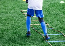 Boys in white and blue football sport form make exercises on green field. Football for children, active lifestyle. Training. Dribble skills royalty free stock images