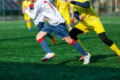 Boys at white yellow sportswear run, dribble, attack on football field. Young Soccer players with ball on green grass. Training. Football, active lifestyle for royalty free stock photos