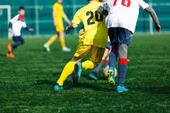 Boys at white yellow sportswear run, dribble, attack on football field. Young Soccer players with ball on green grass. Training. Football, active lifestyle for royalty free stock photo