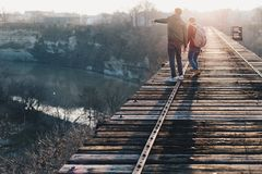 Boys on wooden bridge over river Stock Image