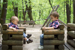 Boys on a wooden train in a park Stock Image