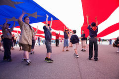 Boyscouts and Cubscouts walk underneath US Flag Royalty Free Stock Images